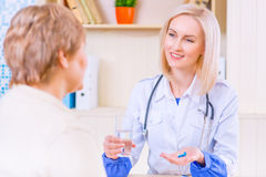 Pleasant nurse speaking with her patient. Best medicines. Pleasant smiling  positive nurse holding pill and glass of water in her hands while giving to her Royalty Free Stock Photos