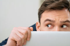 Pleasant office worker hiding behind laptop Stock Images