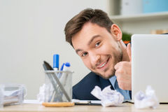 Pleasant office worker hiding behind laptop Royalty Free Stock Images