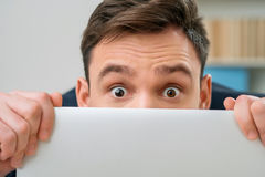 Pleasant office worker hiding behind laptop Royalty Free Stock Image