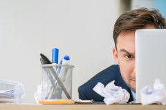 Pleasant office worker hiding behind laptop Stock Photos