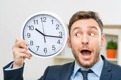 Pleasant office worker holding clock Royalty Free Stock Photos