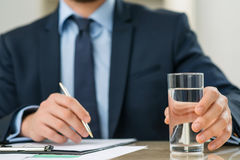 Pleasant office worker holding glass of water Stock Photos
