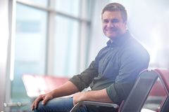 Pleasant optimistic adult male is resting in departure area Royalty Free Stock Photography