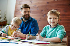 Pleasant paternity moment. Waist-up portrait of family having fun together: two funny little brothers sitting at wooden table and coloring pictures while their stock images