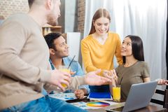 Pleasant people communicating while drinking orange juice. Excellent. Cheerful friendly young students feeling glad while spending time together and Royalty Free Stock Photos
