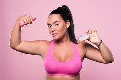 Pleasant plump woman posing on pink background Stock Image