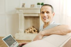 Pleasant positive man feeling good while sitting and smiling. Cheerful person. Handsome cheerful positive man being in a good mood and smiling friendly while Royalty Free Stock Photo