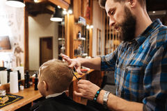 Pleasant professional barber looking at the boys head. New hairstyle. Pleasant professional nice barber looking at the boys head and holding the comb while doing royalty free stock photos