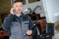 Pleasant professional deliveryman holding mobile phone. Conversation royalty free stock image