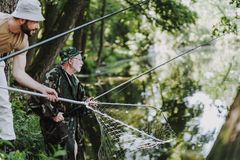 Professional retired angler fishing with his son. Pleasant professional fisherman angling with his son while spending time outdoors stock image