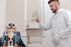 Pleasant professional ophthalmologist choosing the regime Stock Image