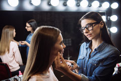 Pleasant professional visagiste applying blush. Healthy skin blush. Pleasant pretty professional visagiste looking at her client and applying blush while putting Stock Images
