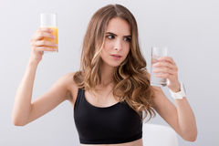 Pleasant puzzled woman holding glasses of water and juice Royalty Free Stock Photo