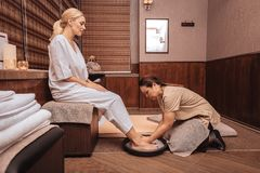 Nice young woman making a bath for feet. Pleasant relaxation. Nice young women making a bath for feet while visiting a spa salon stock photography