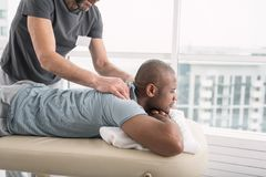 Pleasant good looking man enjoying the massage. Pleasant relaxation. Pleasant good looking men enjoying the massage while visiting the medical center Stock Images