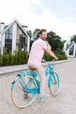 Delighted nice man riding his bike. Pleasant ride. Delighted nice man riding his bike while being in a wonderful mood stock photo