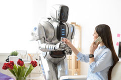 Pleasant robot giving glass of water to girl Royalty Free Stock Photography