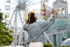 Charming curly girl enjoying scent of flowers. Pleasant scent. Cheerful curly girl lifting up a bouquet and enjoying the scent of flowers while visiting the park royalty free stock photos