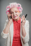 Pleasant senior adult lady with hair curlers using cellphone Royalty Free Stock Images