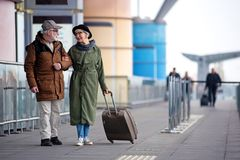 Pleasant senior couple is situating near airport. Enjoy your life. Full length of encouraged calm retired men and women are talking to each other while standing Royalty Free Stock Image