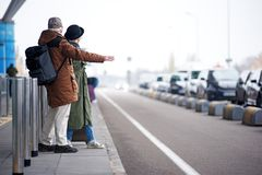 Pleasant senior male and female are waiting for transport. Catch taxi. Full length back view of old couple is standing near road while men with backpack is Royalty Free Stock Photography