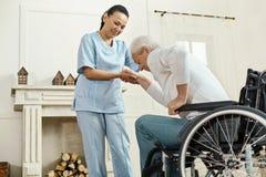 Pleasant senior man holding caregivers hand. Medical assistance. Pleasant good looking senior men holding caregivers hand and getting up from the wheelchair stock photo