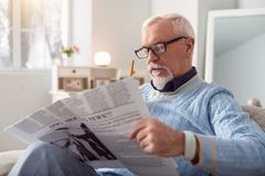 Pleasant senior man reading article in the newspaper. Informative article. Charming elderly men in eyeglasses reading an article in the newspaper and marking royalty free stock images