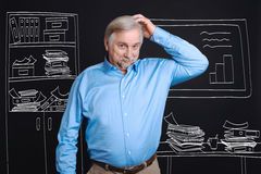Pleasant senior man scratching his head. Lots of work. Pleasant optimistic senior man standing in his office and scratching his head while having a heavy Stock Image