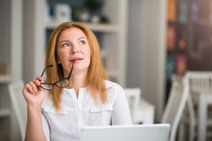 Pleasant senior woman sitting at the table Stock Image