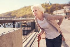 Pleasant senior woman suffering from lower back pain. Sharp pain. White-haired senior lady standing on the bridge and touching her sore lower back while looking Royalty Free Stock Photos