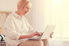 Pleasant senior woman using her laptop at home Stock Photos