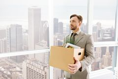 Pleasant serious employee standing in the office Royalty Free Stock Image