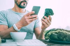 Pleasant serious man making different photos of vegetables royalty free stock photos