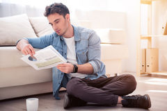Pleasant  serious man sitting on the floor Stock Image