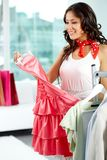 Pleasant shopping. Portrait of happy girl choosing new dress in clothing departmant Royalty Free Stock Photos