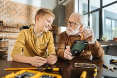 Pleasant skillful man passing his skills. Sharing knowledge. Pleasant nice skillful men sitting together with his grandson and telling him how to fix things Stock Photography