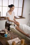 Pleasant skillful masseuse working in the spa salon. Massage session. Pleasant skillful masseuse having a massage session while working in the spa salon Royalty Free Stock Photo
