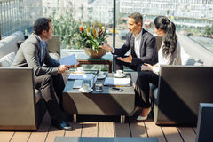 Pleasant smart entrepreneurs talking to each other. Business meeting. Delighted smart pleasant entrepreneurs sitting around the table and talking to each other Royalty Free Stock Photography