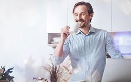 Pleasant smiling adult man drinking coffee at home Royalty Free Stock Images