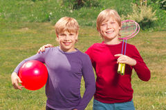 Pleasant smiling boys holding sport equipment Stock Photography