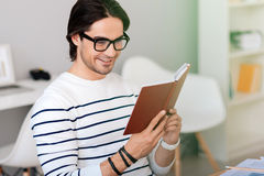 Pleasant smiling man reading book Stock Photo