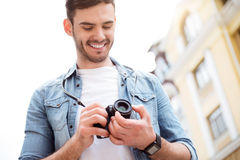 Pleasant smiling man standing in the street. Ready to make shots. Positive smiling man holding photo camera and going to take photos while expressing gladness royalty free stock photography