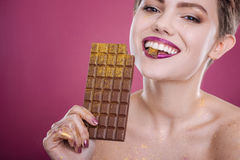 Pleasant smiling woman eating chocolate bar Stock Image
