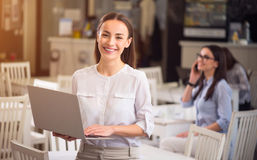 Pleasant smiling woman holding laptop. Full of emotions. Pleasant delighted overjoyed smiling woman holding laptop and expressing gladness while people sitting royalty free stock photography