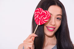 Pleasant smiling woman holding lollypop Stock Photo