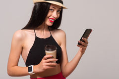 Pleasant smiling woman standing isolated on grey background. Share your emotions. Positive delighted woman holding cell phone and drinking coffee while stock photos