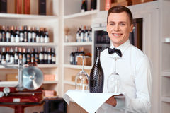 Pleasant sommelier holding tray with wine bottle. Welcoming guests. Cheerful positive handsome waiter holding tray with wine bottle while being involved in work Stock Photos
