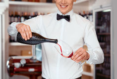 Pleasant sommelier pouring wine into wineglasses Stock Photography