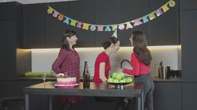 Pleasant surprise for adult woman at her Birthday. Joyful mother having fun hiding gift box from peeping daughter in party cap during Birthday celebration in stock video footage